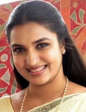 Sukanya with a smiling face, wearing earrings, and a necklace.