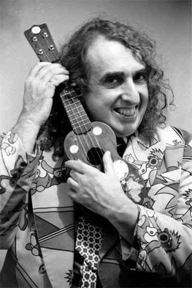 Tiny Tim with curly hair, wearing a suit and holding a ukelele.