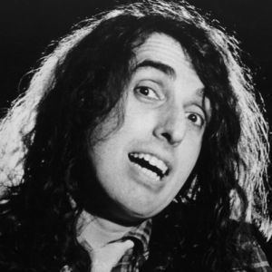 Tiny Tim with curly hair and wearing a checkered suit.