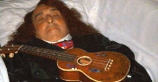 Tiny Tim lying on his coffin, wearing a suit and a ukelele on top of him.