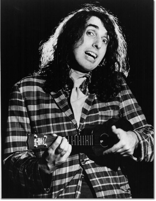 Tiny Tim with curly hair, wearing a checkered suit and playing a ukelele.