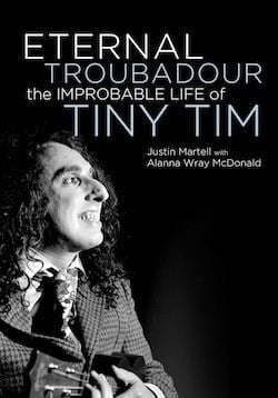 Poster of Tiny Tim with curly hair, wearing a checkered suit and playing a ukelele.