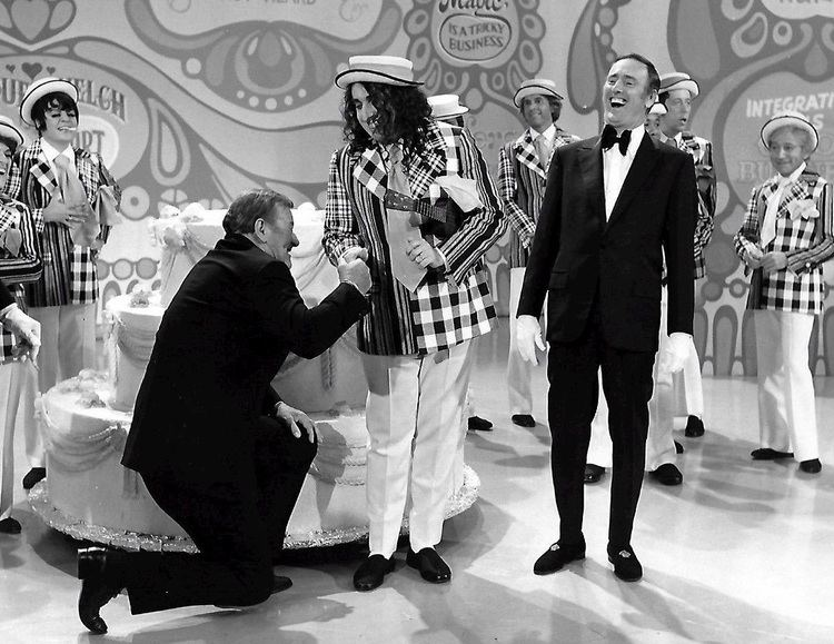A variety show hosted by Dan Rowan and Dick Martin featuring Tiny Tim wearing a white hat, a checkered suit, white pants, black shoes, and holding a ukelele.