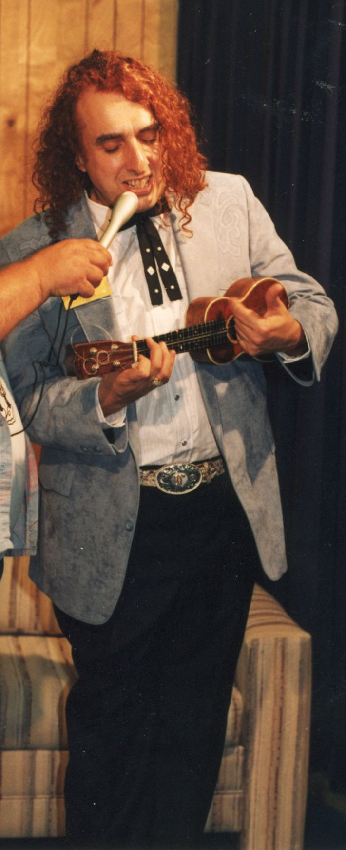 Tiny Tim with curly blonde hair, wearing a suit, a white shirt, black pants, and playing a ukelele with a man holding a microphone for him.