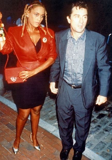 Robert De Niro wearing blue coat and striped long sleeves & Toukie Smith in her braided hair, red coat, black dress and red bag