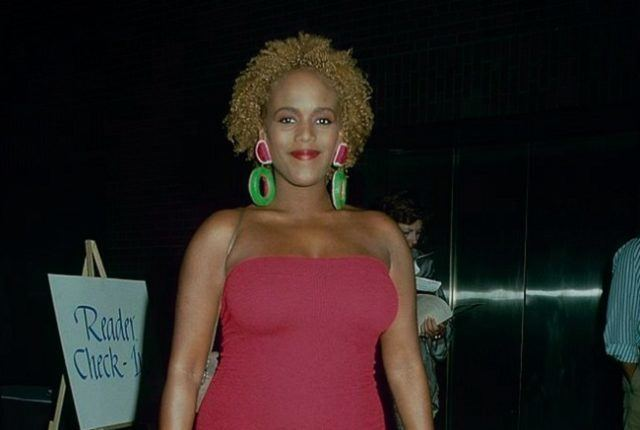 Toukie Smith in her curly hair while wearing pink dress and pink and green earrings