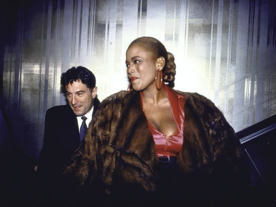 Toukie Smith in her braided hair with Robert De Niro who is wearing black coat, white long sleeves and neck tie