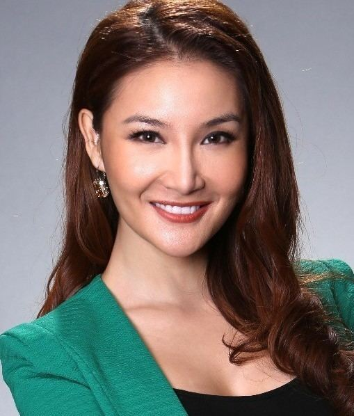 Tracey Chang wearing green coat and black inner top