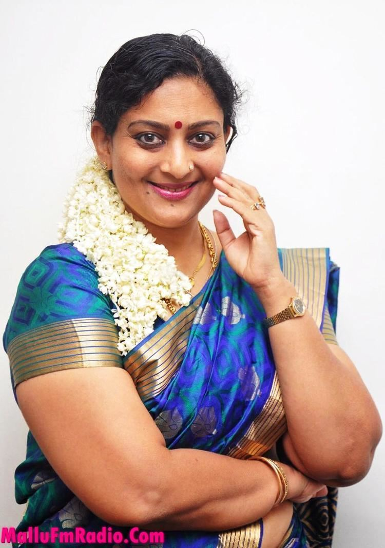 Unni Mary, a malayalam old actress in a white background wearing a dress