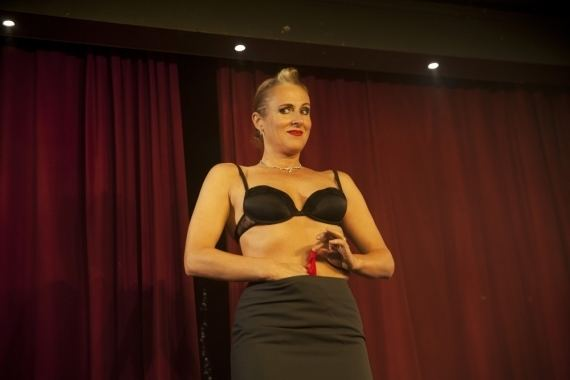 Ursula Martinez performing on stage while wearing a black brassiere and skirt.