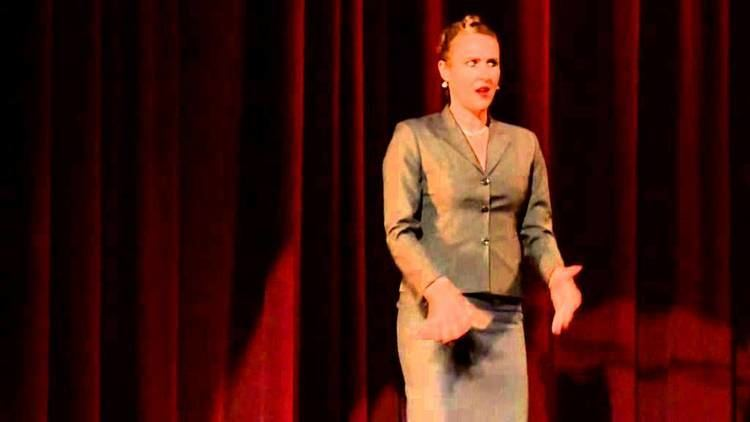 Ursula Martinez wearing long sleeves and a skirt while performing on stage.