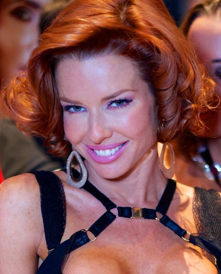Veronica Avluv wearing a black sexy top and earrings with curly blonde hair.