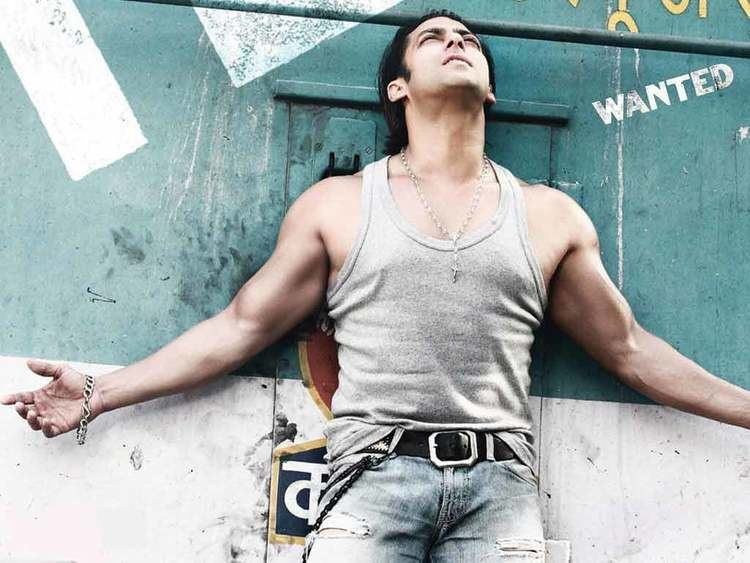 Salman Khan with his arms wide open while wearing a gray sando, jeans, necklace, and bracelet