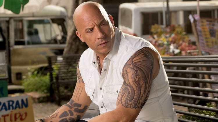 Vin Diesel wearing white sleeveless polo in a scene from the 2017 movie, XXX: Return of Xander Cage